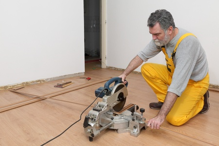 worker cut wooden batten for laminate floor,  floating wood flooring